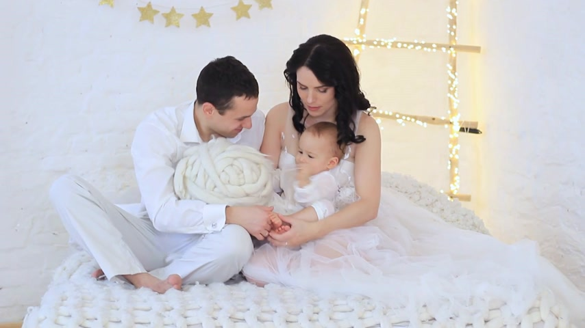 dad, mom and little son all in white are played in the studio Stock Footage