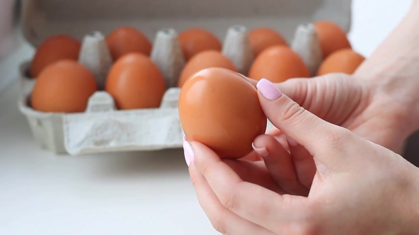 пищевой продукт : Female hands with chicken eggs in cardboard