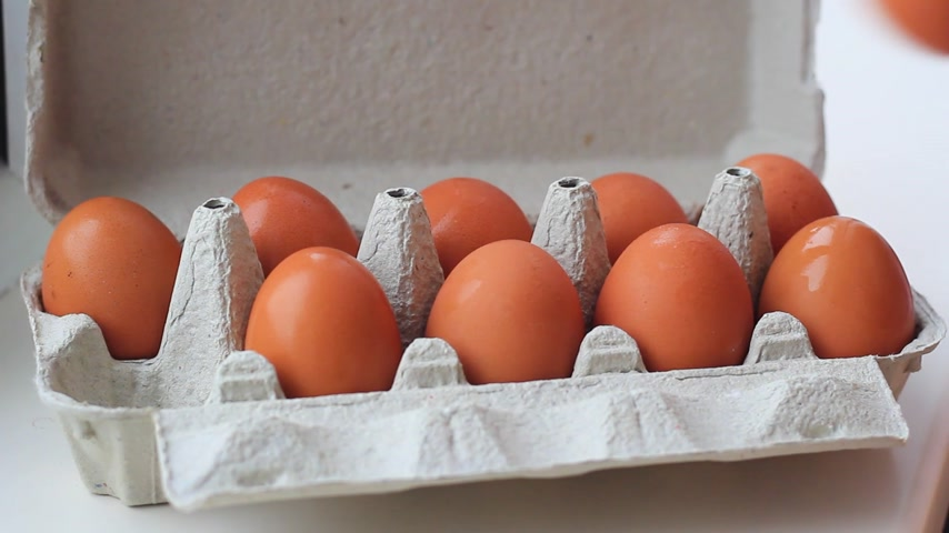 Female hands with chicken eggs in cardboard