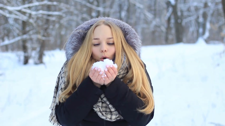 Beautiful blonde girl in the winter season is playing with snow