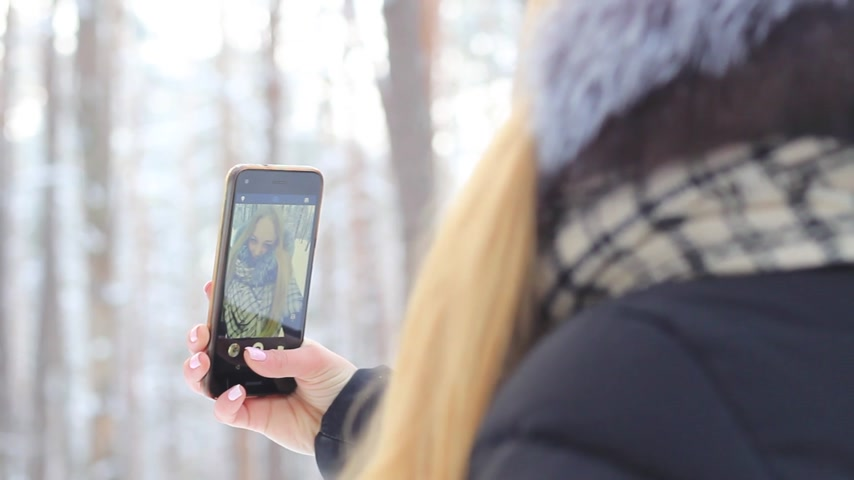 Girl in a snowy forest with a phone in the reflection rejoices having fun Stok Video