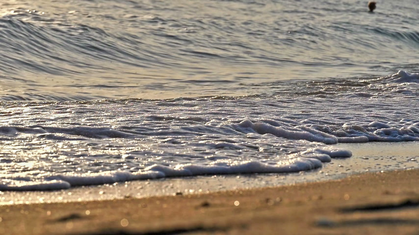 seixo : beach wave splashing macro in sunset slow motion