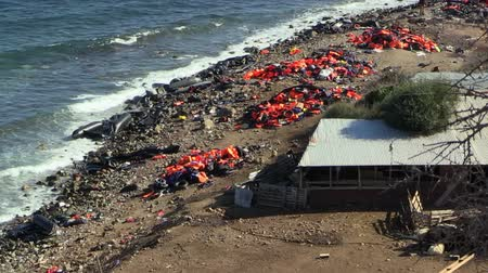 переполох : LESVOS, GREECE - NOV 2, 2015: Abandoned by the refugees belongings and life jackets on the shore.