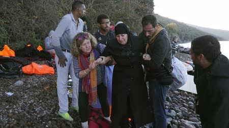 lifesavers : LESVOS, GREECE - NOV 5, 2015: Volunteers help refugee woman to go on shore.