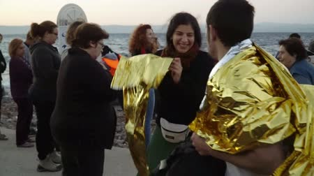 переполох : LESVOS, GREECE - NOV 5, 2015: Volunteers give the refugees a warm foil to keep warm. Everning.