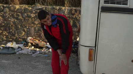 переполох : LESVOS, GREECE - NOV 5, 2015: Refugee is heated near the exhaust pipe of the bus.