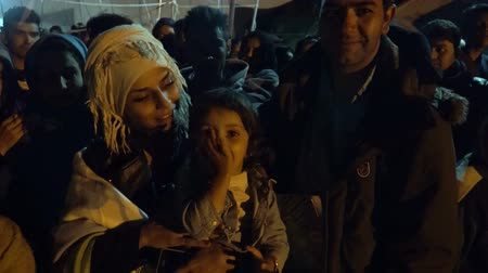 lifesavers : LESVOS, GREECE - NOV 5, 2015: Afghan refugee family in the queue for the bus to the camp at night.