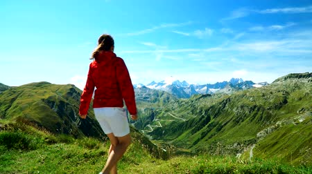 A pretty girl enters the place with a beautiful view and rejoices at the Furka pass in the Swiss Alps. Wideo