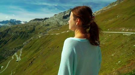 Cute girl watching the panoramic view from the Furka pass in the Swiss Alps.