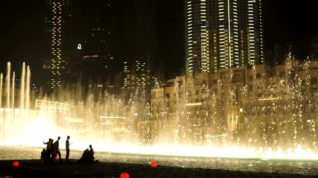 khalifa : DUBAI, UAE - 19 MARCH 2018 : Dubai Water Fountain near Burj Khalifa illuminated by the city at night. Stock Footage