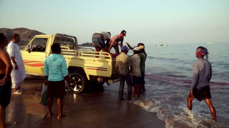 Fishermen from the UAE drag the net with fish in the back of the car. Al Akah Beach, Fujairah.
