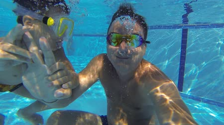 plunging : Boy and father diving in swimming pool. GoPro shoot underwater Stock Footage