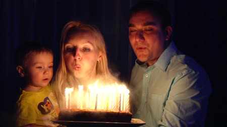 cakes : Happy family blowing candles on a birthday cake, slow motion Stock Footage