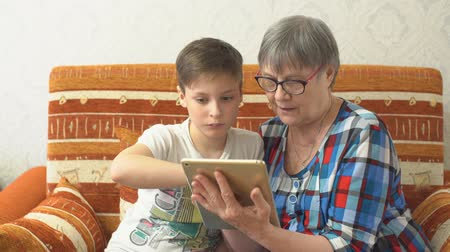 grandchild : Grandson teaches grandmother to play in a tablet Stock Footage