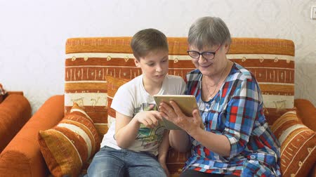бабушка : Grandmother and Grandson Using Tablet for Entertainment While Sitting on The Sofa at Home