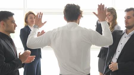 dát : group of businessmans celebrating a success. the man give a high five to a colleague. slow motion