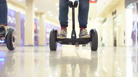 gyro : Teenager on hyroscooter in a modern shopping center. Close up of mans legs on two wheels electric gyro scooter