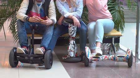gyro : A group of teenagers with hyroscooter in the mall. The guy uses a mobile phone in the company of friends Stock Footage