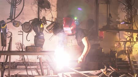 smithy : Welder in the mask works in the workshop. Blacksmith forges on the anvil. brutal man working at the forge with metal. slow motion