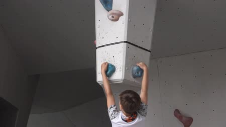 把持 : Boy climbs on a rock on the climbing wall. young athletic hung upside down on an artificial rock. slow motion