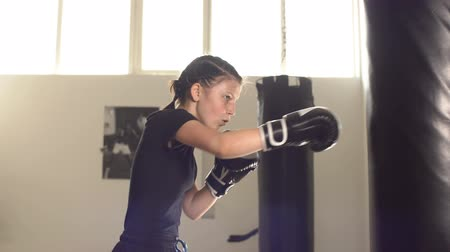 eğitici : Teen girl in boxing gloves is working out a blow on the punching pear