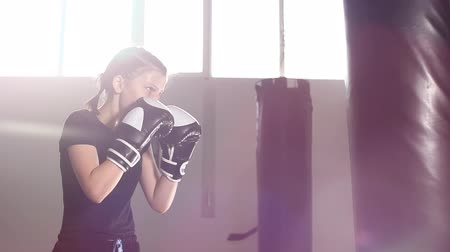 хит : Teen girl in boxing gloves is working out a blow. Slow motion Стоковые видеозаписи
