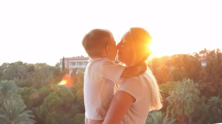 сумерки : Happy mother and son laughing and kissing at sunset. Slow motion Стоковые видеозаписи