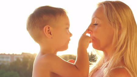 mother love : Young mother playing with baby son at sunset. Slow Motion Stock Footage