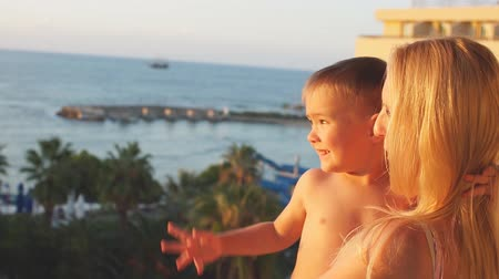 сумерки : Young mother playing with baby son at sunset. Slow Motion Стоковые видеозаписи