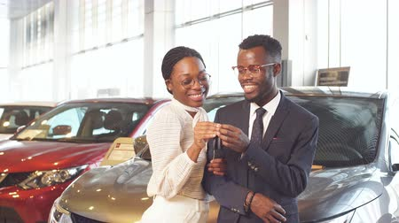 bérlet : Happy couple buying new car in showroom.