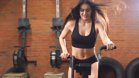 koncentracja : Fit young woman using air bike at the gym.