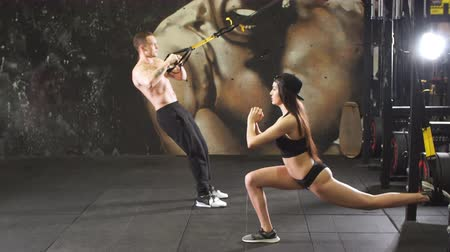 весить : Young sporty couple workout in gym with elastic trx equipment.