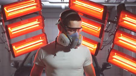 detailing : Man wearing protective mask and glasses holding polishing machine with red warm lights in background.