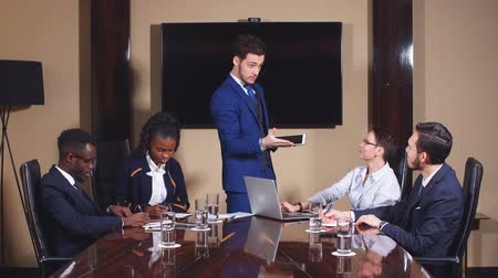 Businessman presenting to colleagues at a meeting.