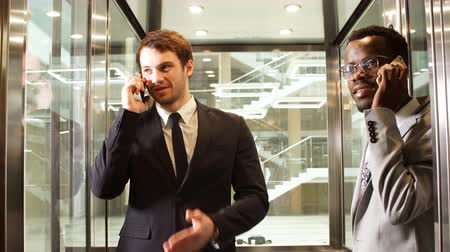 Two multinational Business man standing in elevator and use smartphone. Business people in large glass elevator in modern office.