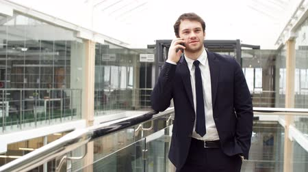 Enthusiastic Business man while talking on mobile phone. Stock mozgókép