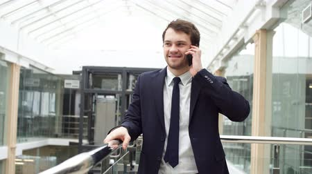 Smiling modern young businessman speaking on the phone while walking.