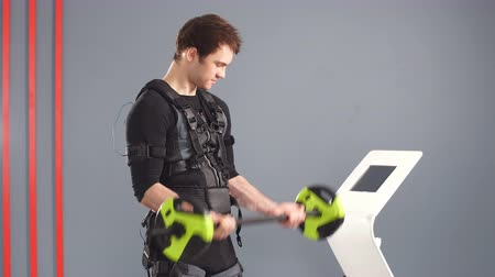 Fit Man wearing black electrostimulation suit lifting barbell.