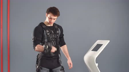 Man in Electrical Muscular Stimulation suit standing with dumbbells near ems tablet and push on screen.