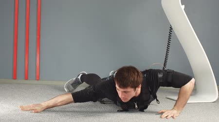 EMS male working out, doing push ups while connected to electric muscle stimulator.