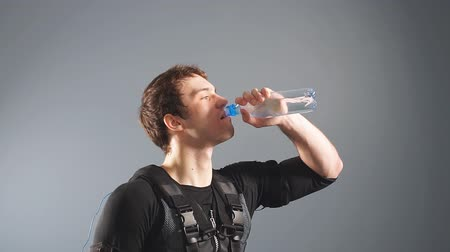 Fit man wearing electro stimulation suit drink water after training.