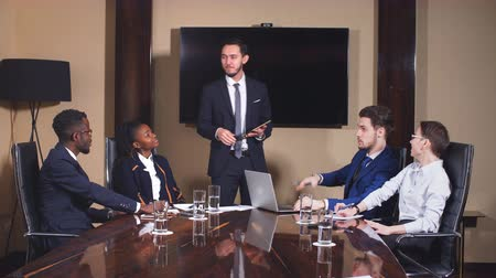 afro americana : Businessman presenting to colleagues at a meeting.