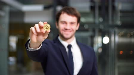 Golden Bitcoin in hand with businessman blurred on background. Stock mozgókép