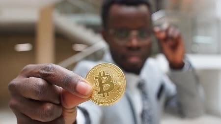 afro americana : Golden Bitcoin in African Man Hand. Businessman Holding Digitall Symbol of New Virtual Currency.