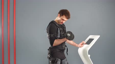 Fit man in Electrical Muscular Stimulation suit standing with dumbbells.