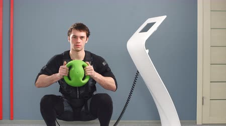 Fit Man in EMS suit training with medecine bal, Stock Footage