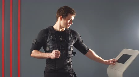 Male athlete pushing on screen on ems machine regulating intensity. Stock Footage