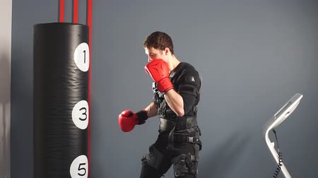 Fit man in boxing gloves during training. Boxer in suit of electric stimulation in gym.