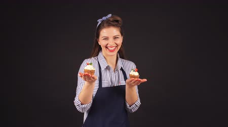 Young woman pastry chef with cupcakes in hand smiling at the camera. Vídeos