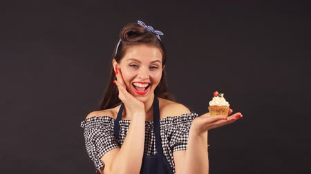 украшать : Young woman pastry chef with cupcakes in hand smiling at the camera